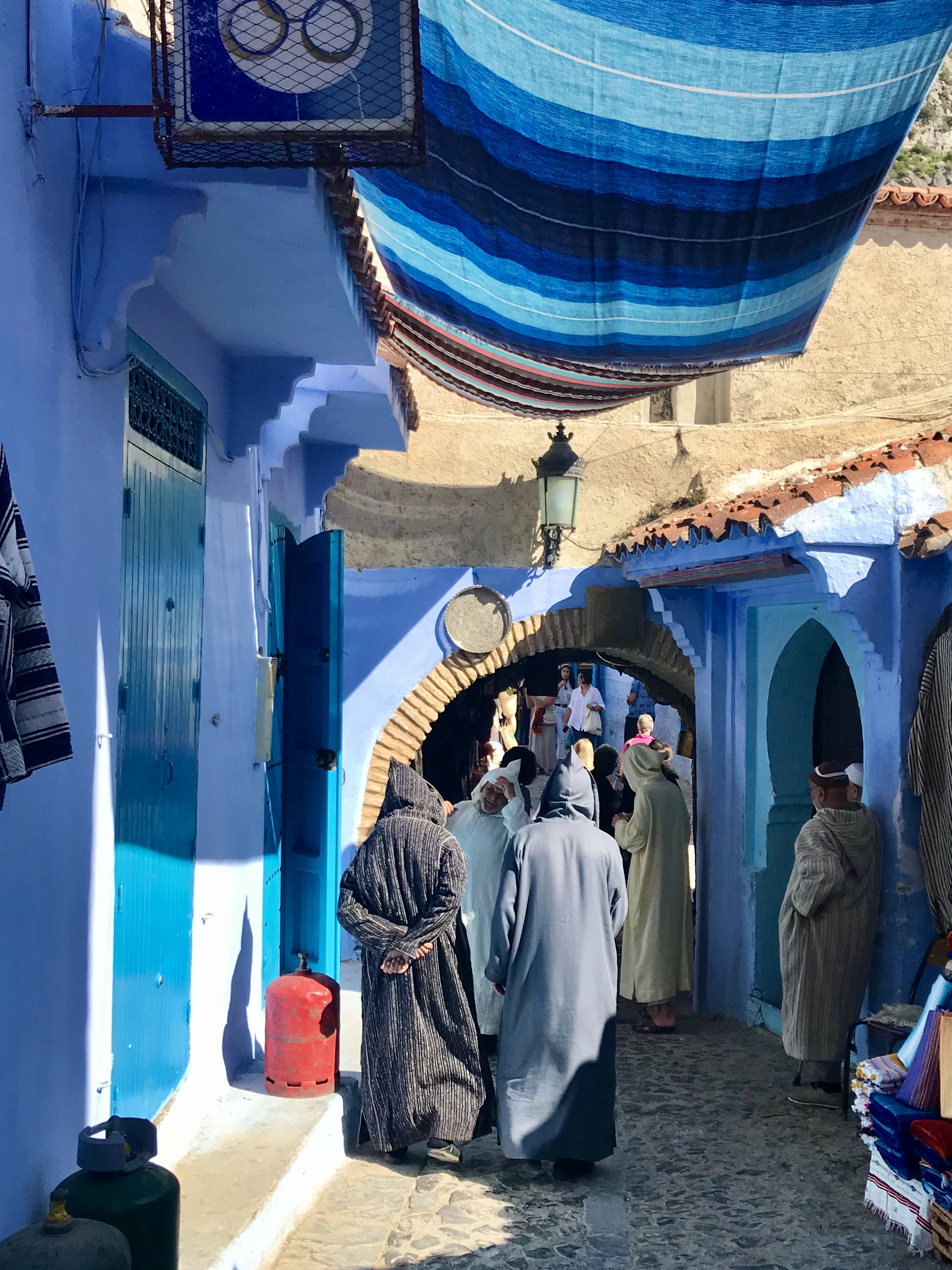Two men in robes walking back streets of Chefchaouen