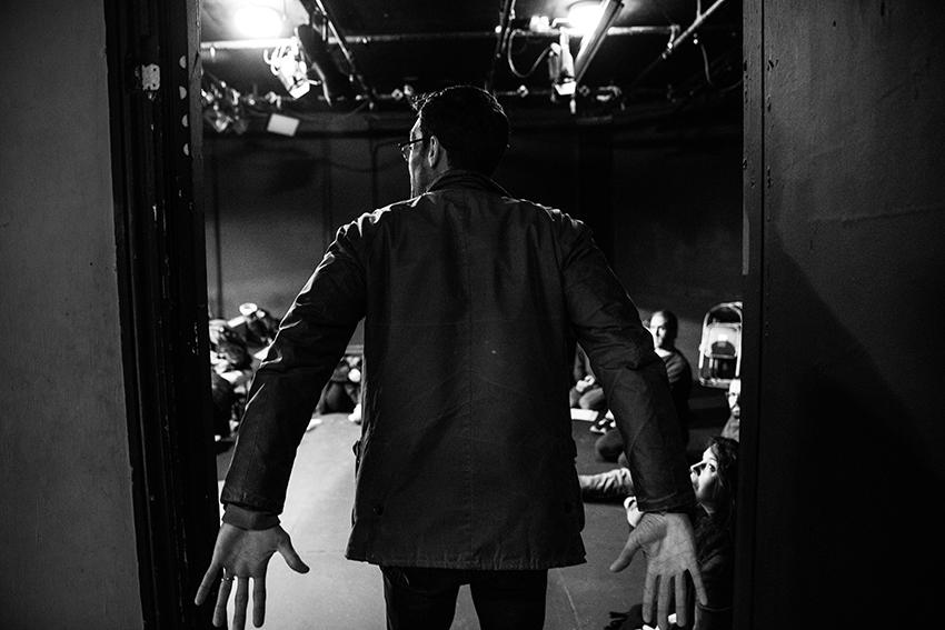 Man walking through a doorway to stage