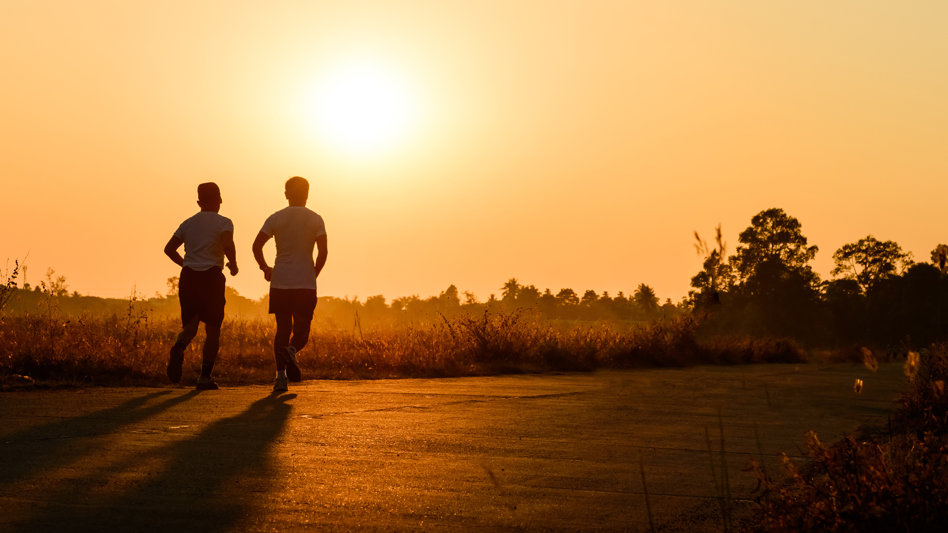 Two people running toward a sunset