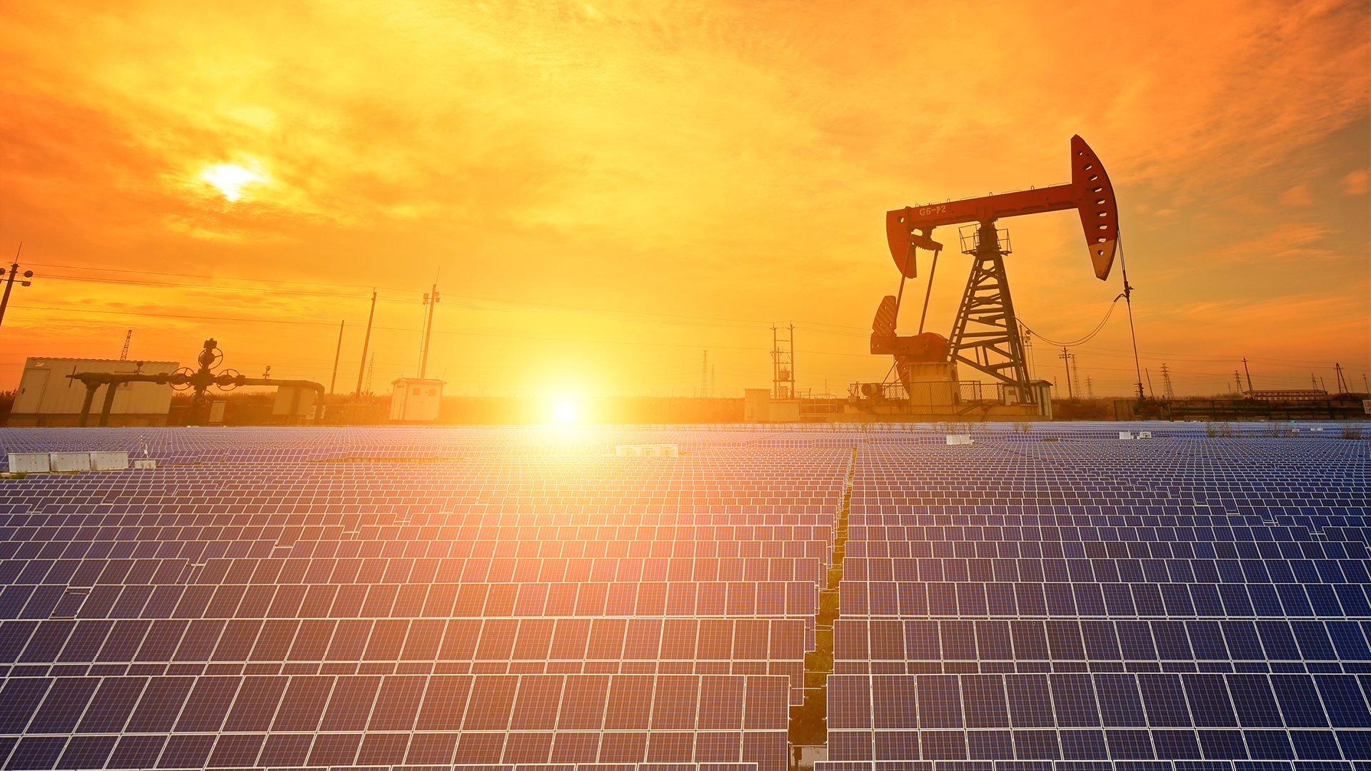 Solar panels near oil field overlooking a sunset