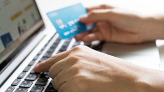 hand in laptop and credit card