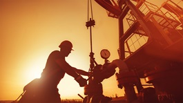 Oil worker checking the oil pump on the sunset