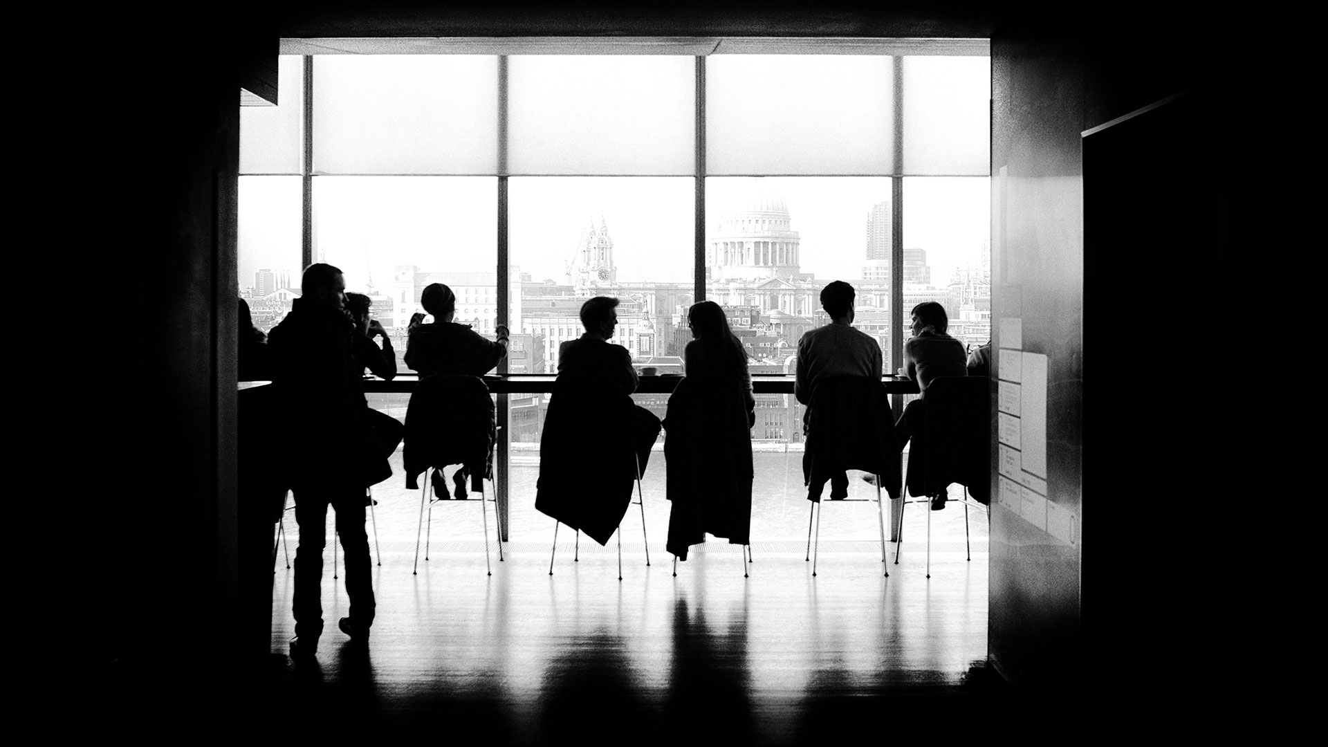 Group of people in black and white looking at the London skyline