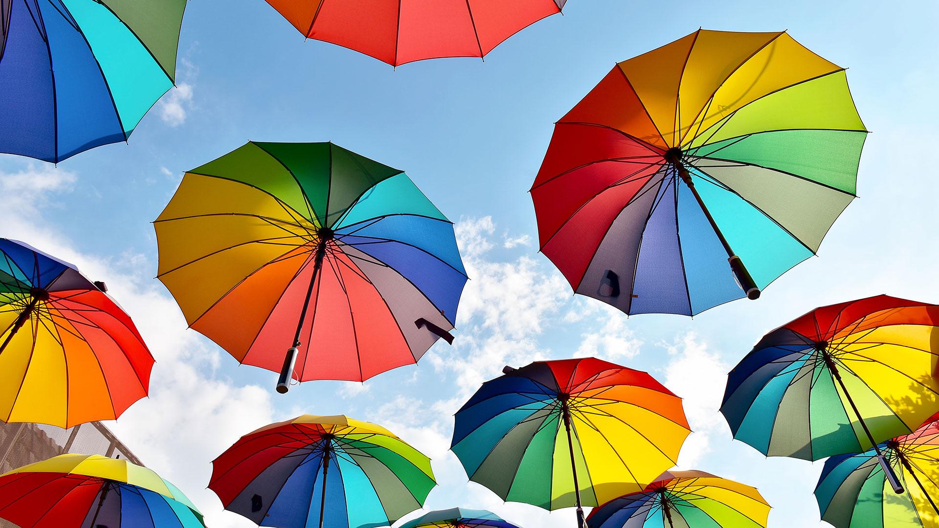 Rainbow coloured umbrellas in the blue sky