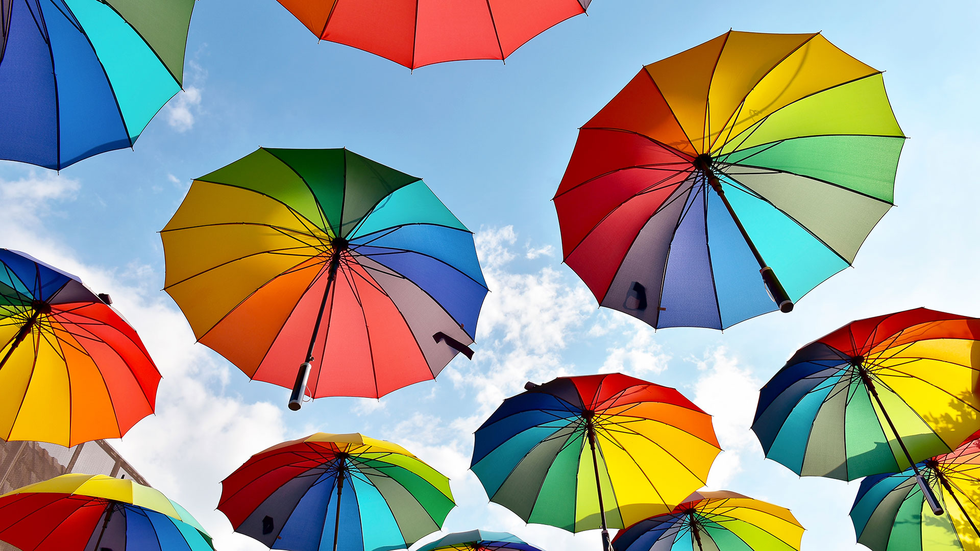 Image of multi-colored open umbrella's floating in sky
