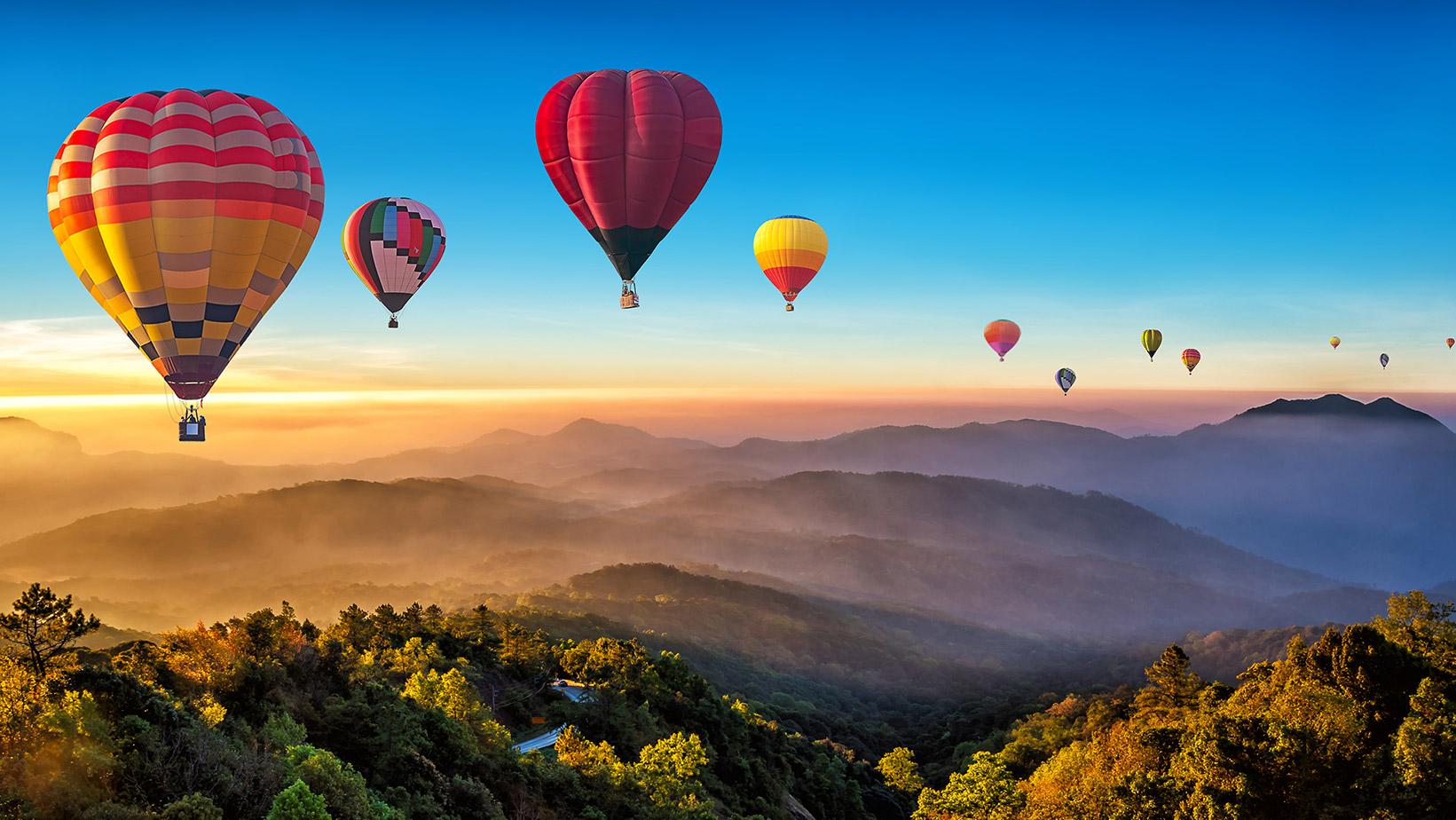 Balloons flying over a mountain range