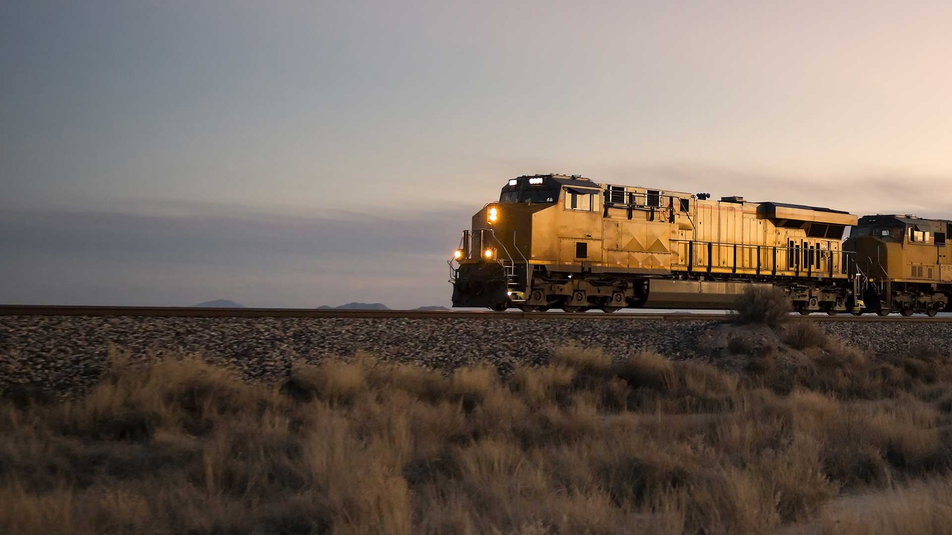 cargo train travelling through rural area at twilight
