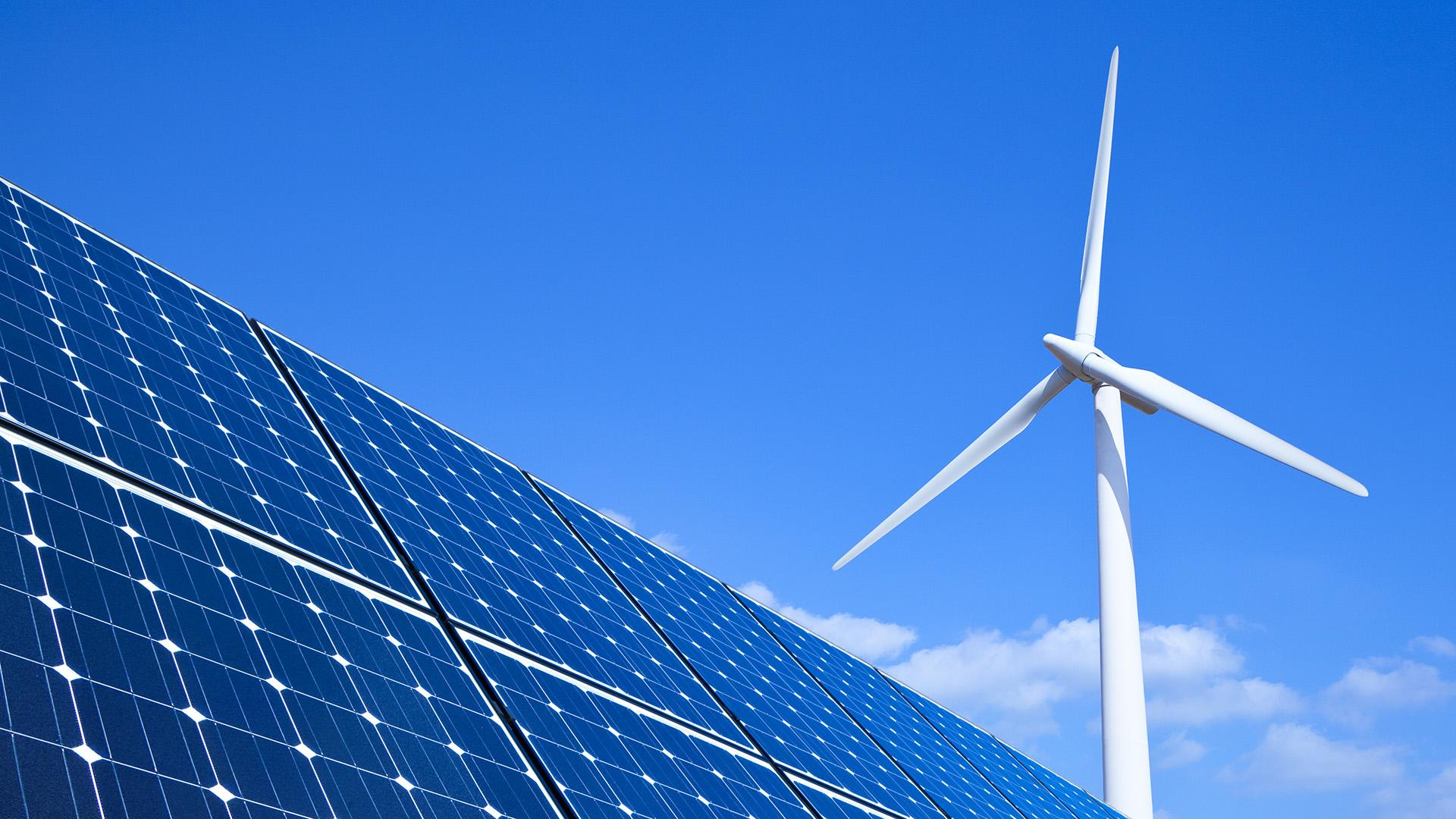 Solar panel and turbine under blue sky