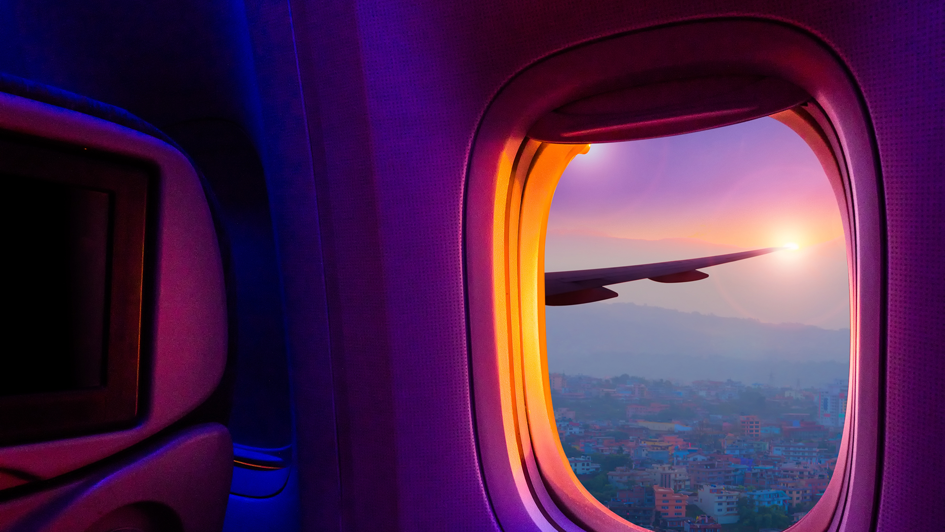Airplane seat and open window looking out onto the wing and sunset