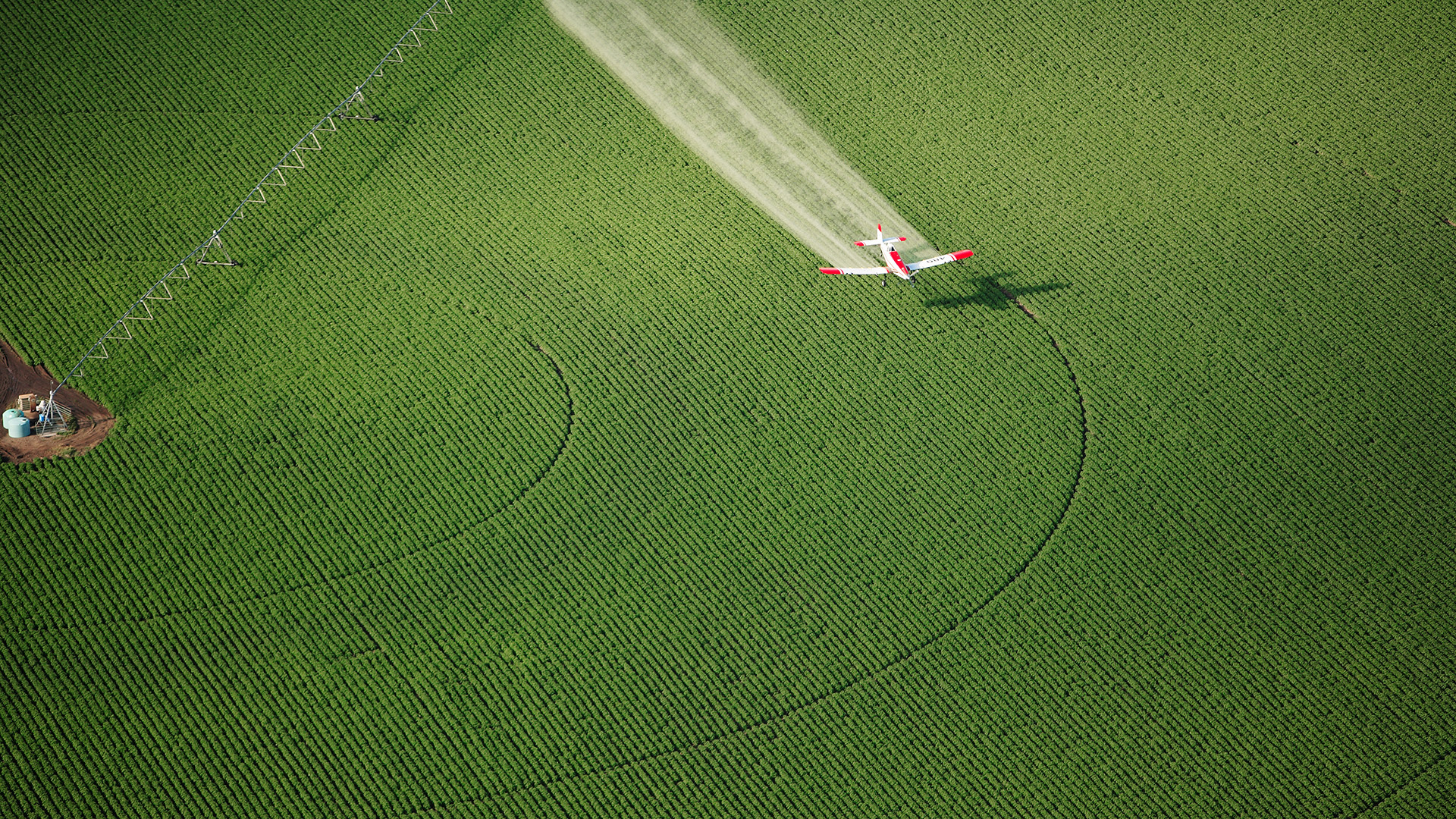 Image of a plane flying over a field