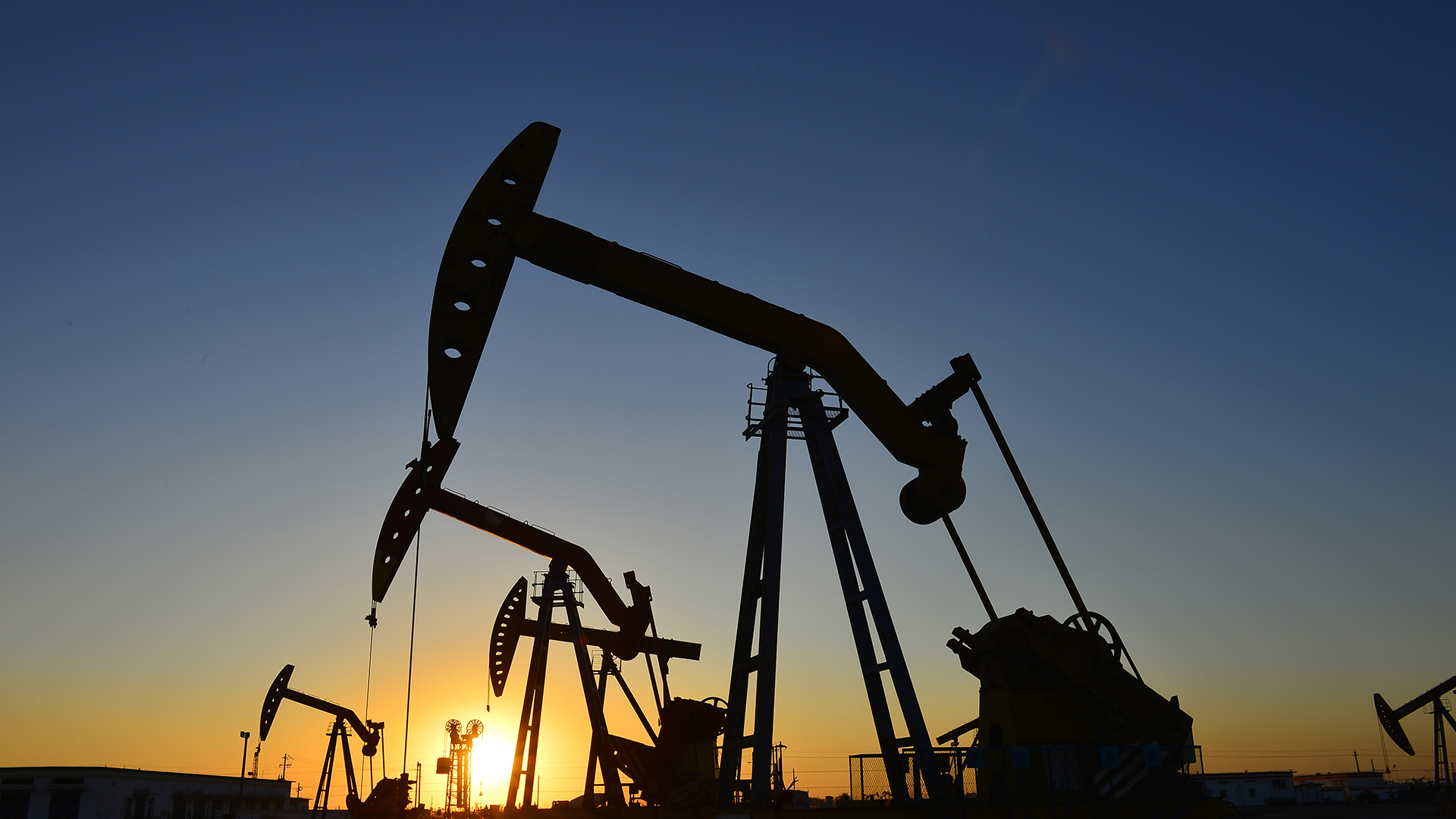 A line of three oil drills at sunset.