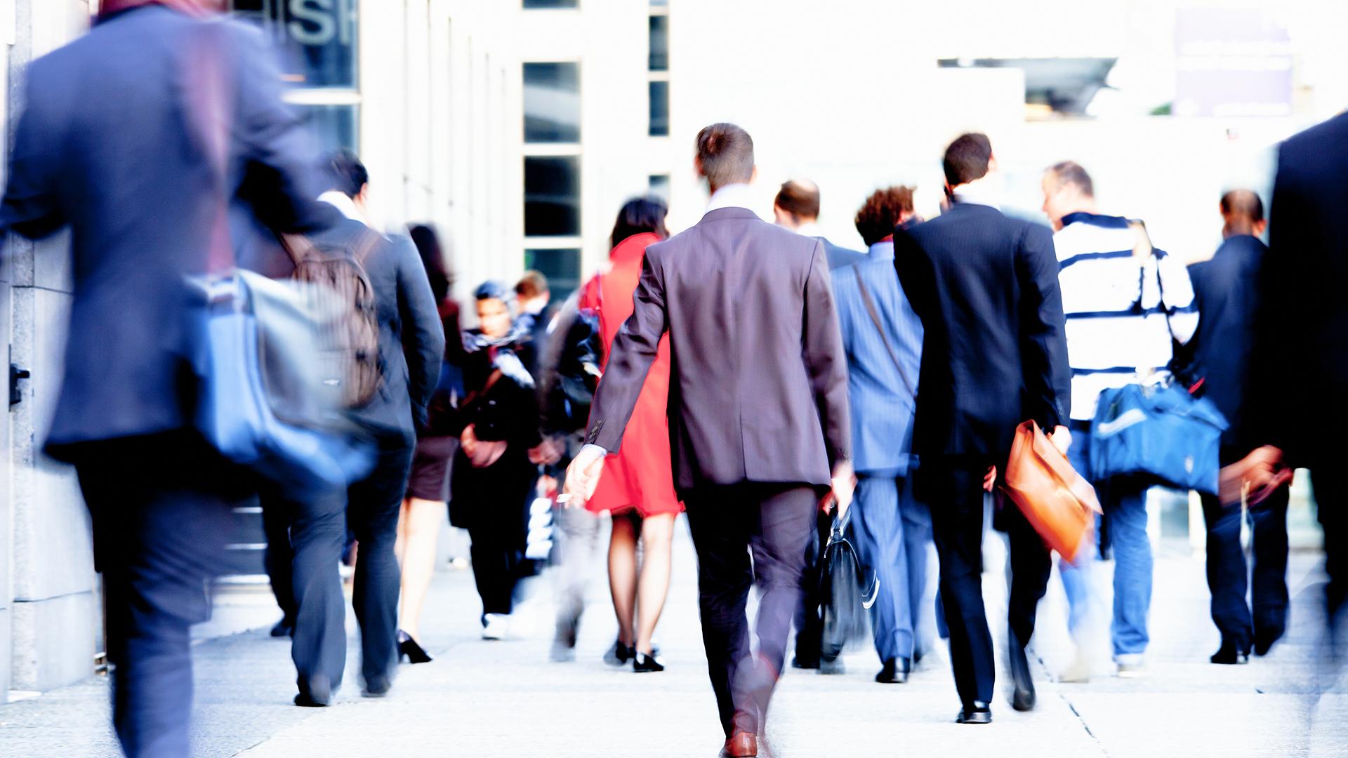 Commuters walking on sidewalk