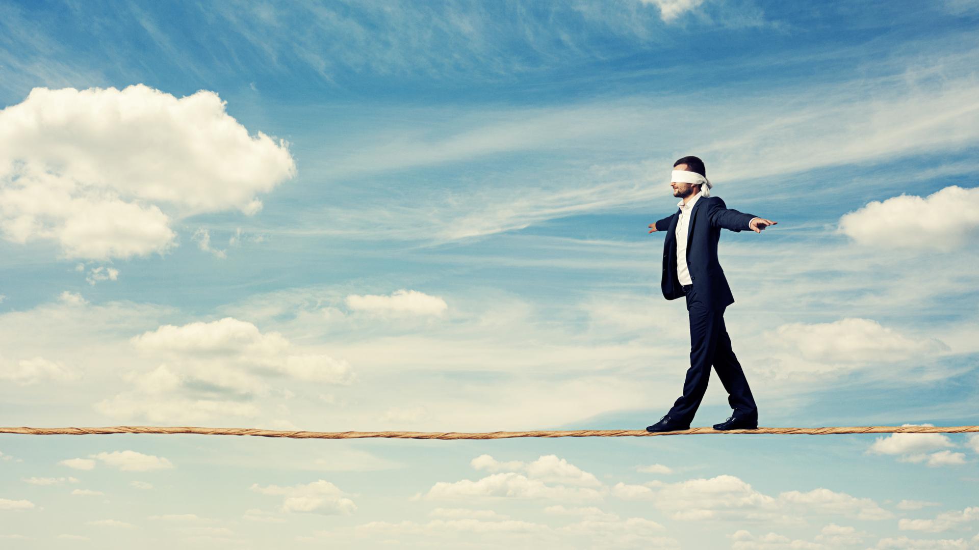 man walking blindfolded on tightrope