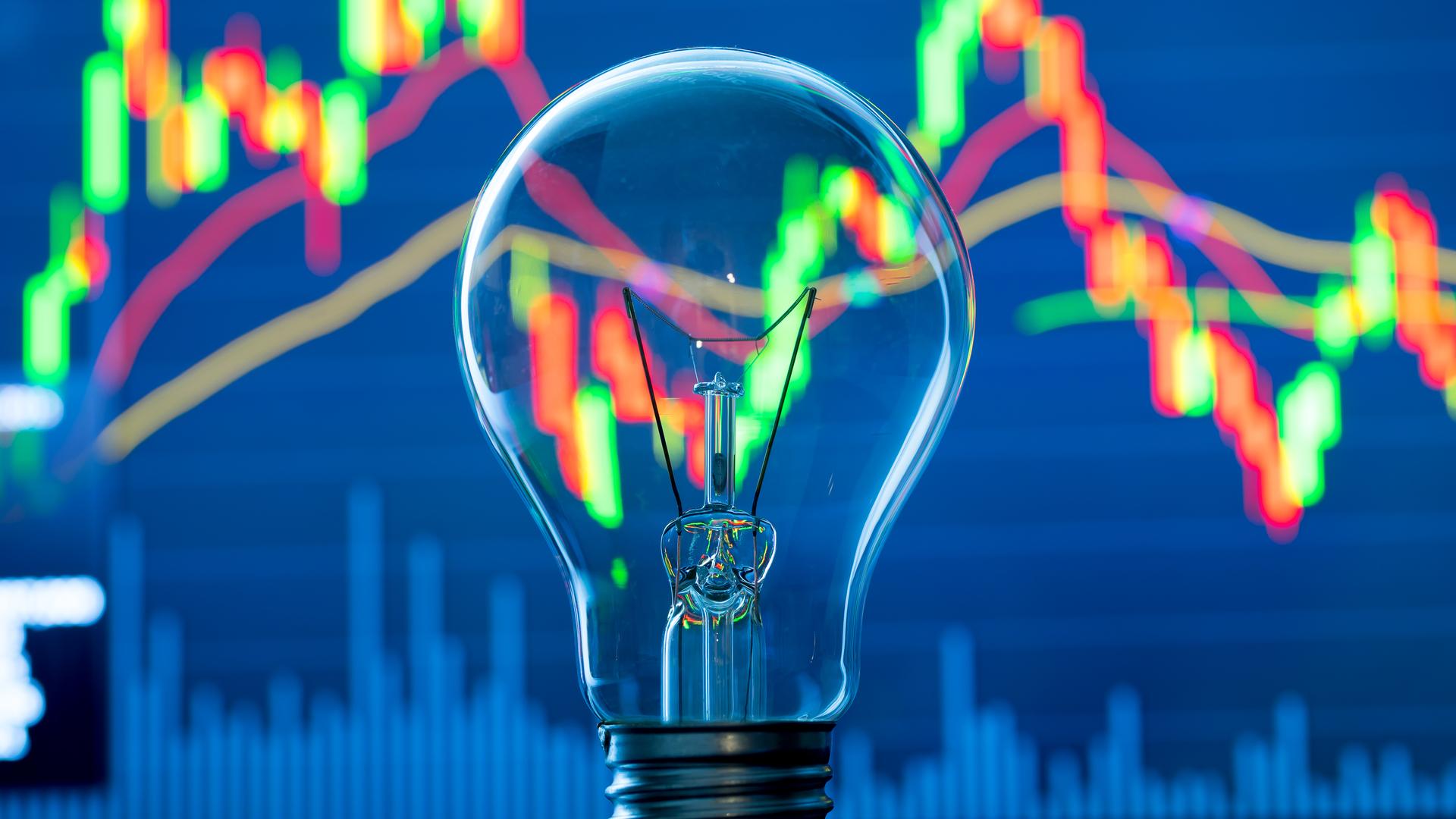 lightbulb in front of stocks screen