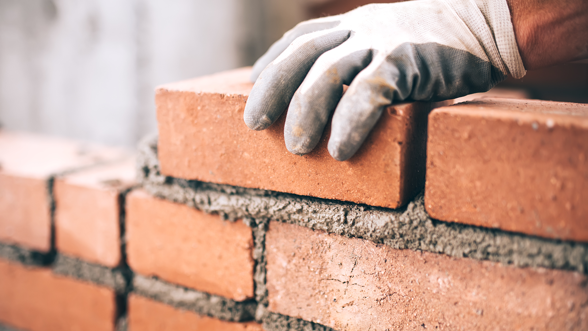 Close up of industrial bricklayer installing bricks on construction site