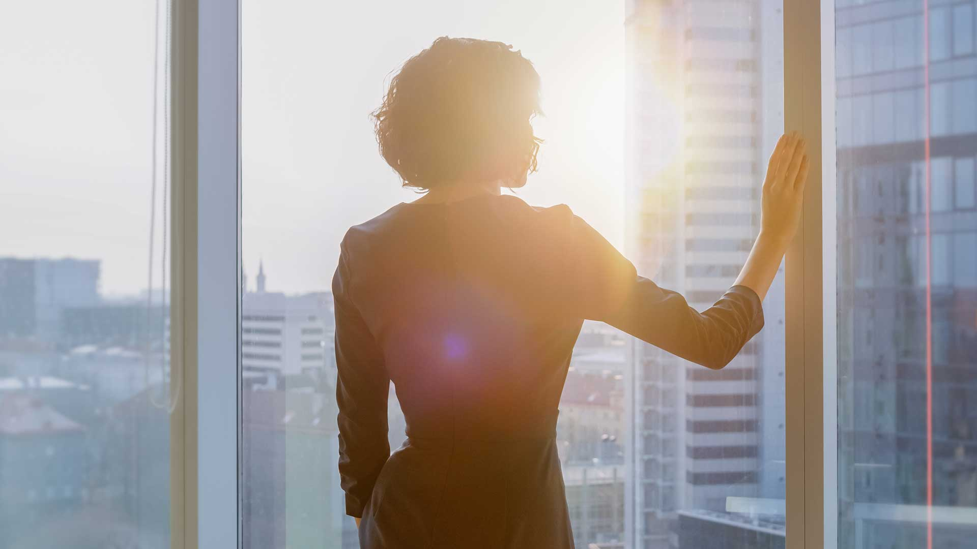 Shot of the Successful Businesswoman in a Striking Black Dress in Her Office Looking out of the Window at Sunset. Modern Business Office with Personal Computer and Big City View