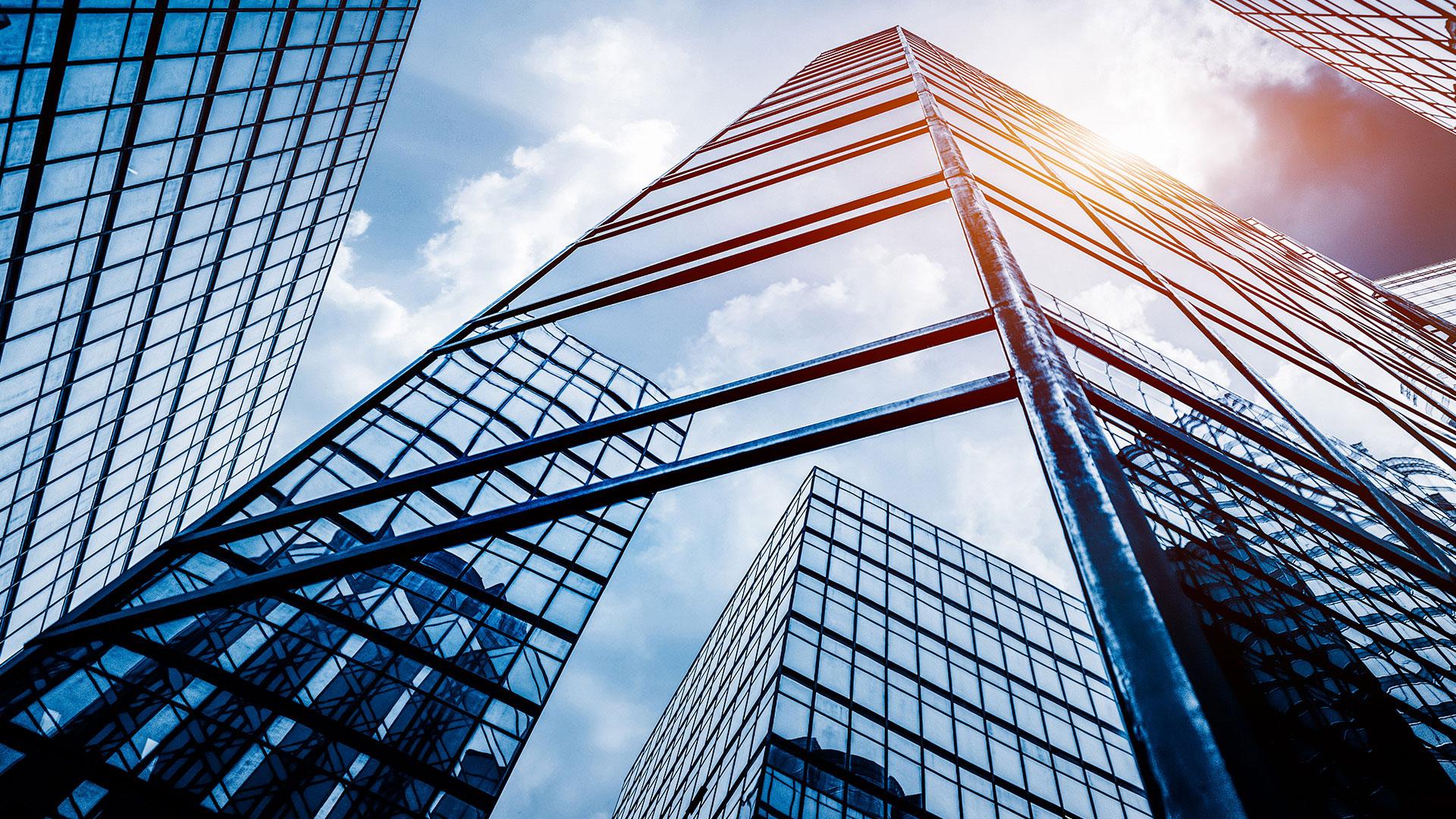 Immeuble de bureaux en verre dont le reflet projette le ciel et d'autres tours