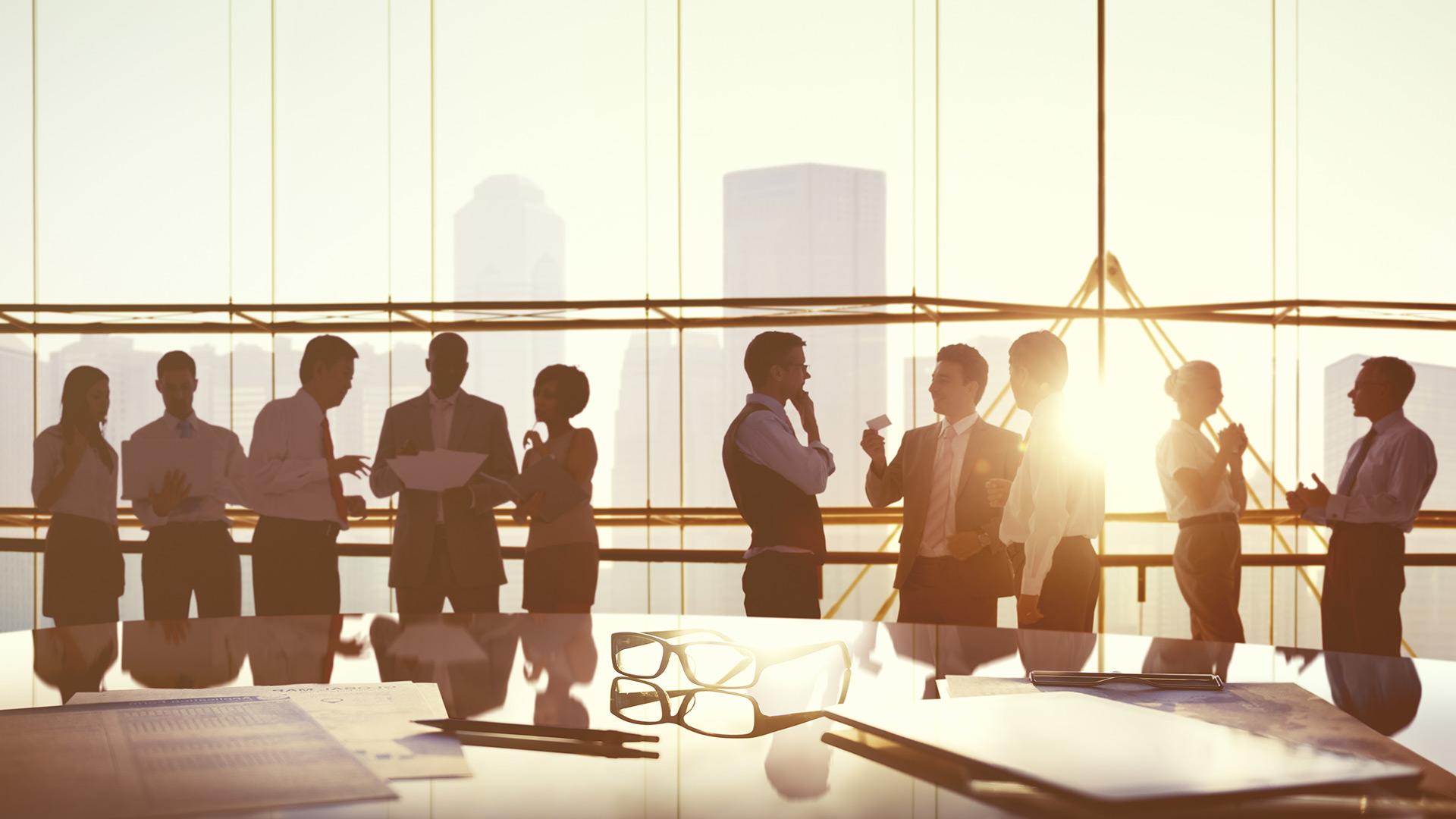 Gens qui discutent debout autour d'une table de conseil d'administration, coucher de soleil en arrière-plan