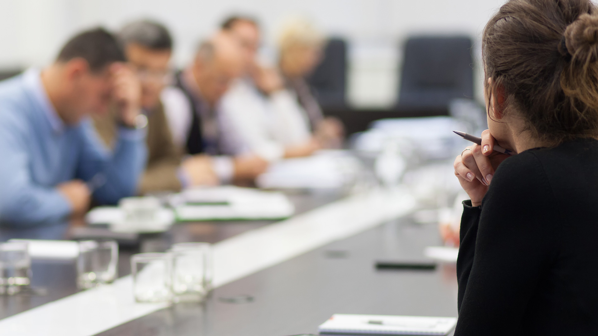 Woman's profile looking at boardroom table of people working