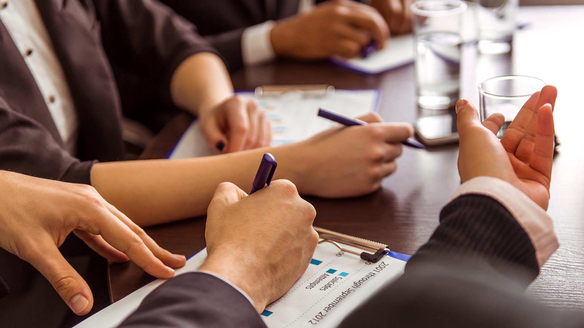 Gros plan sur des mains qui tiennent des stylos sur une table de réunion