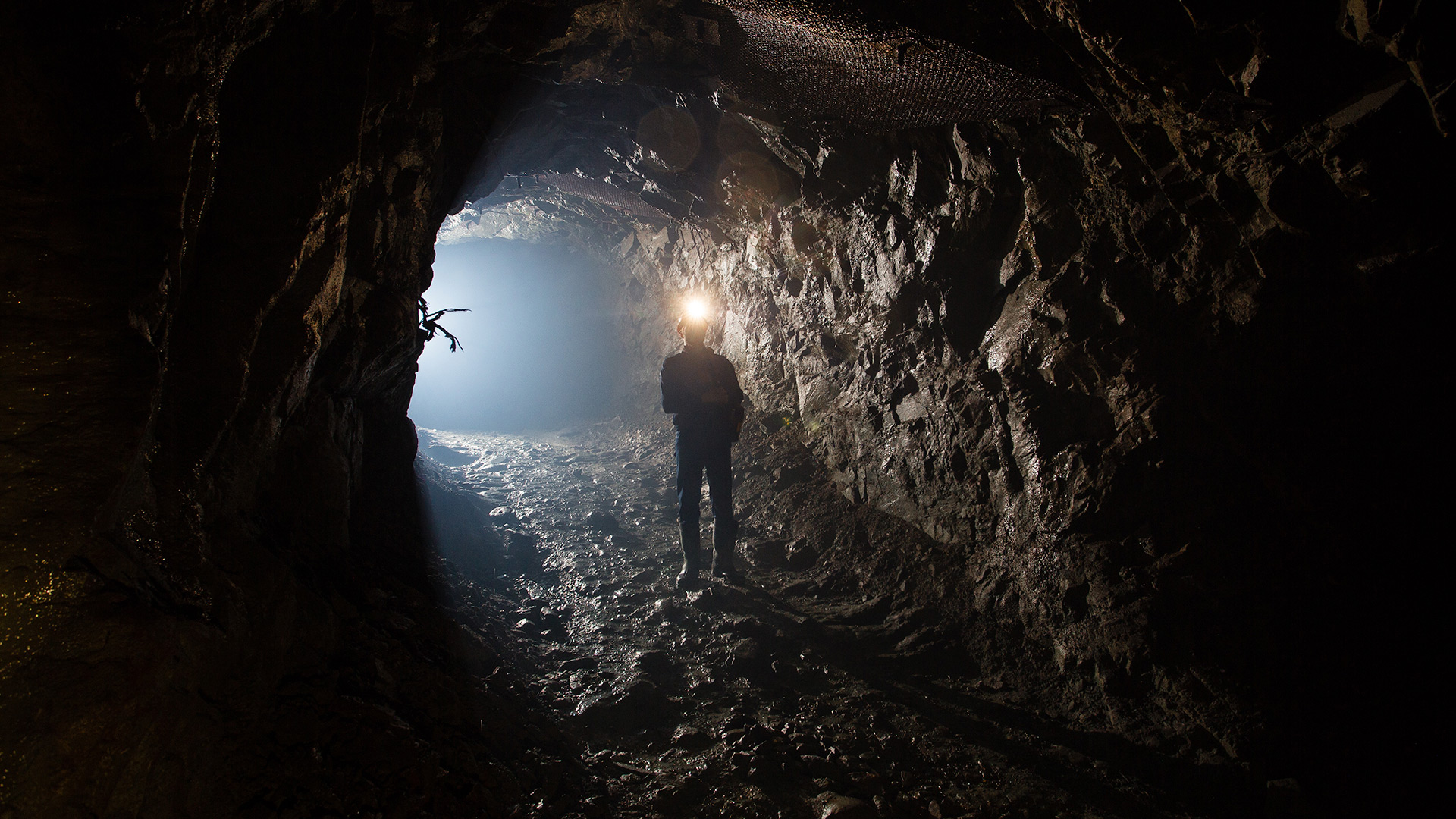 A miner standing in a mine tunnel with his headlight on