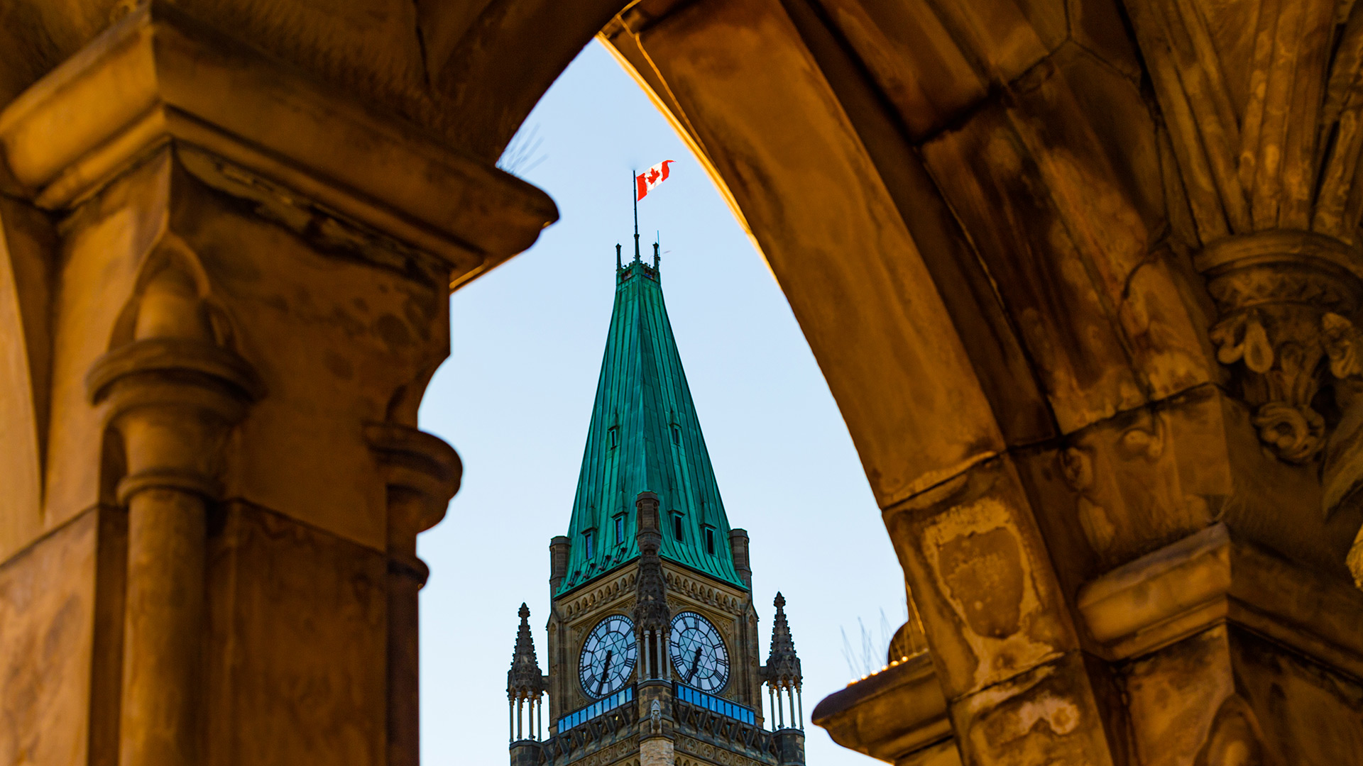 Canadian flag on top of Parliament building peeking through arch of other building