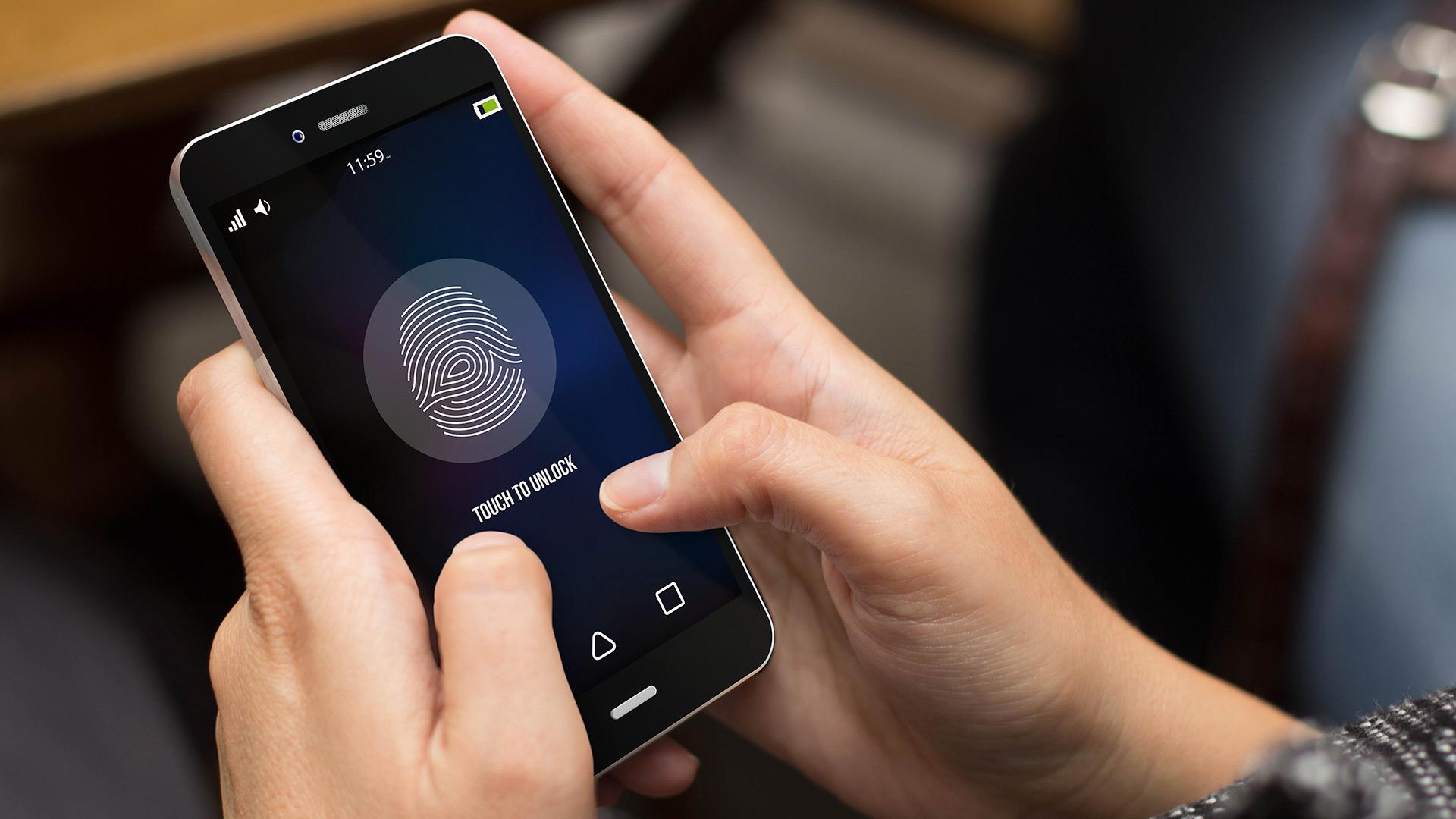 Main qui tient un téléphone cellulaire qui affiche l'écran verrouillé avec l'identification par empreintes digitales