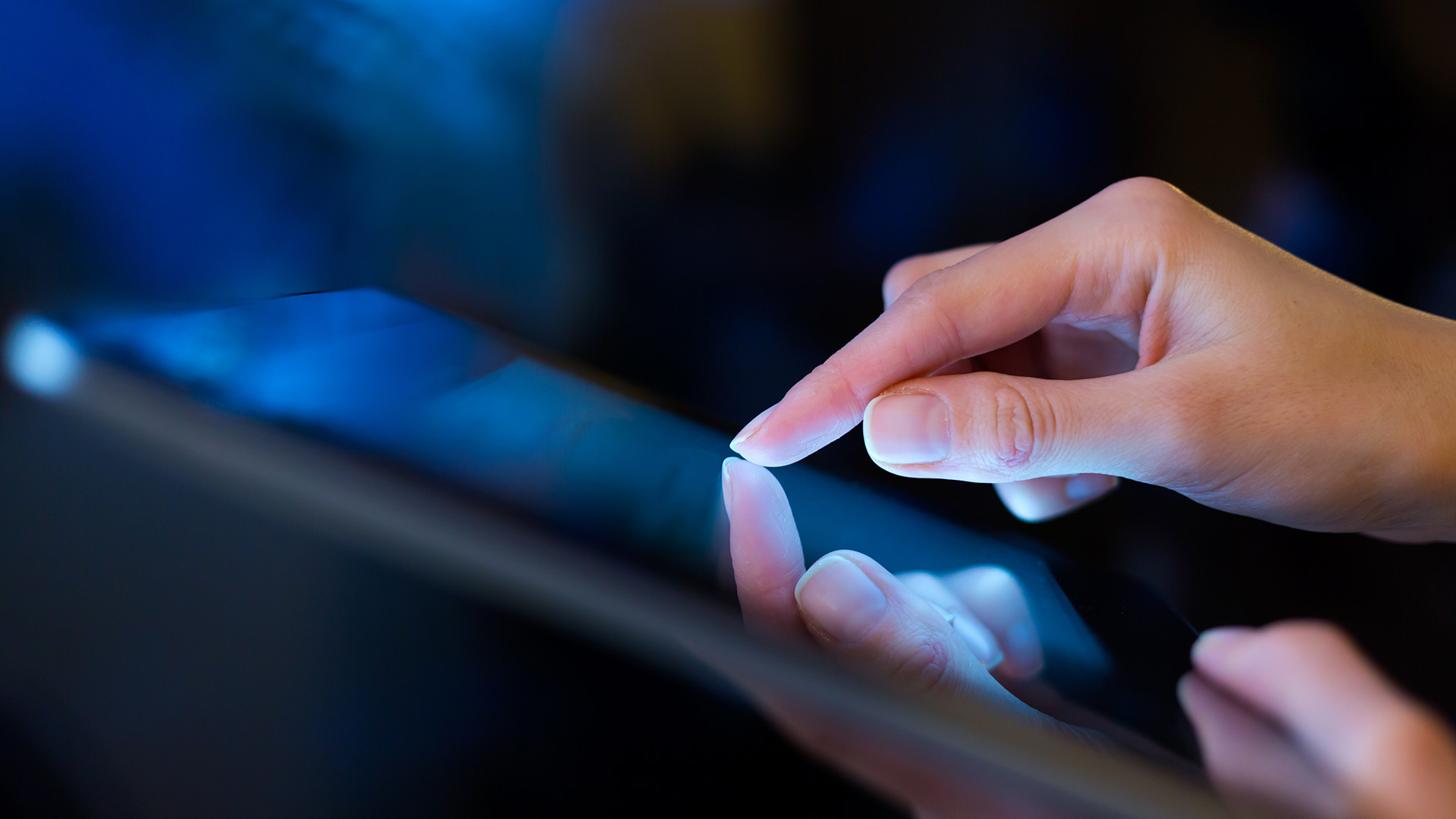 Close-up of hand scrolling on tablet