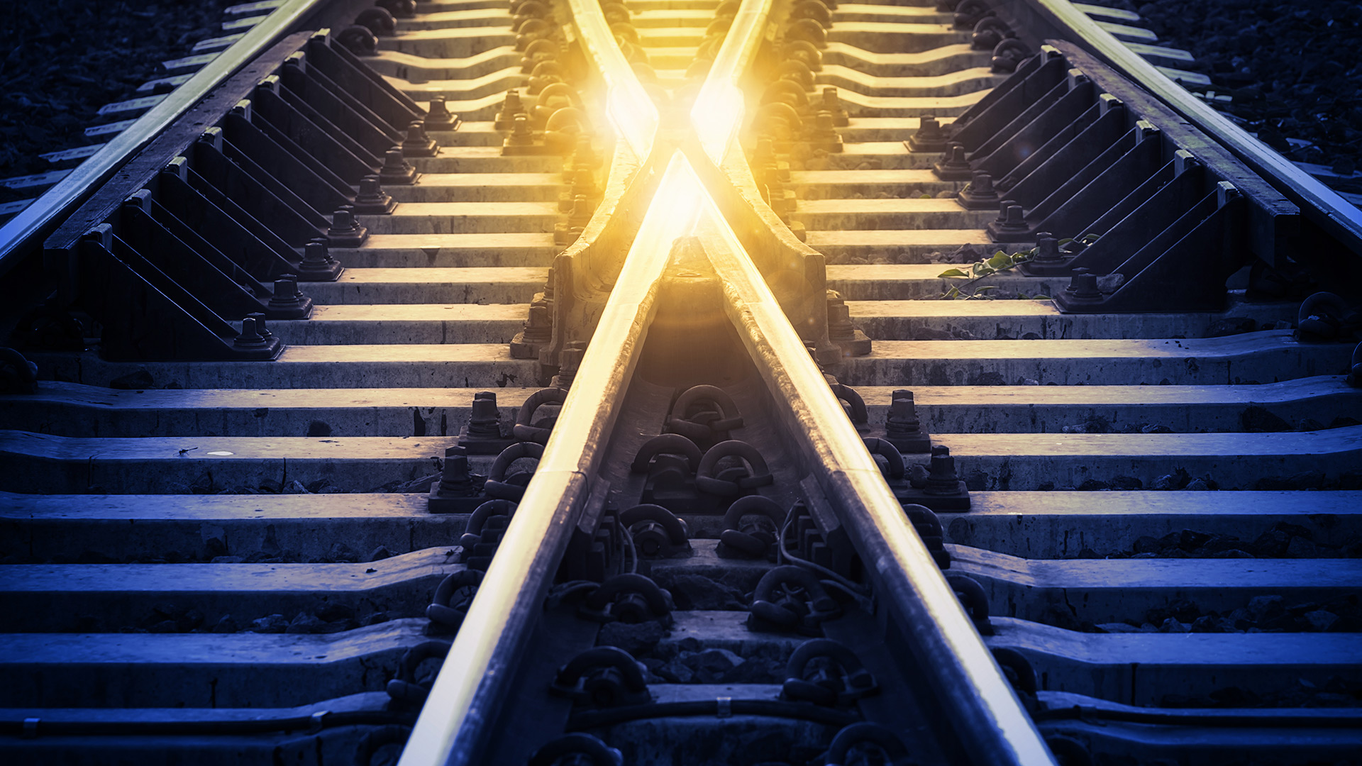 A light shining on two rail tracks coming together
