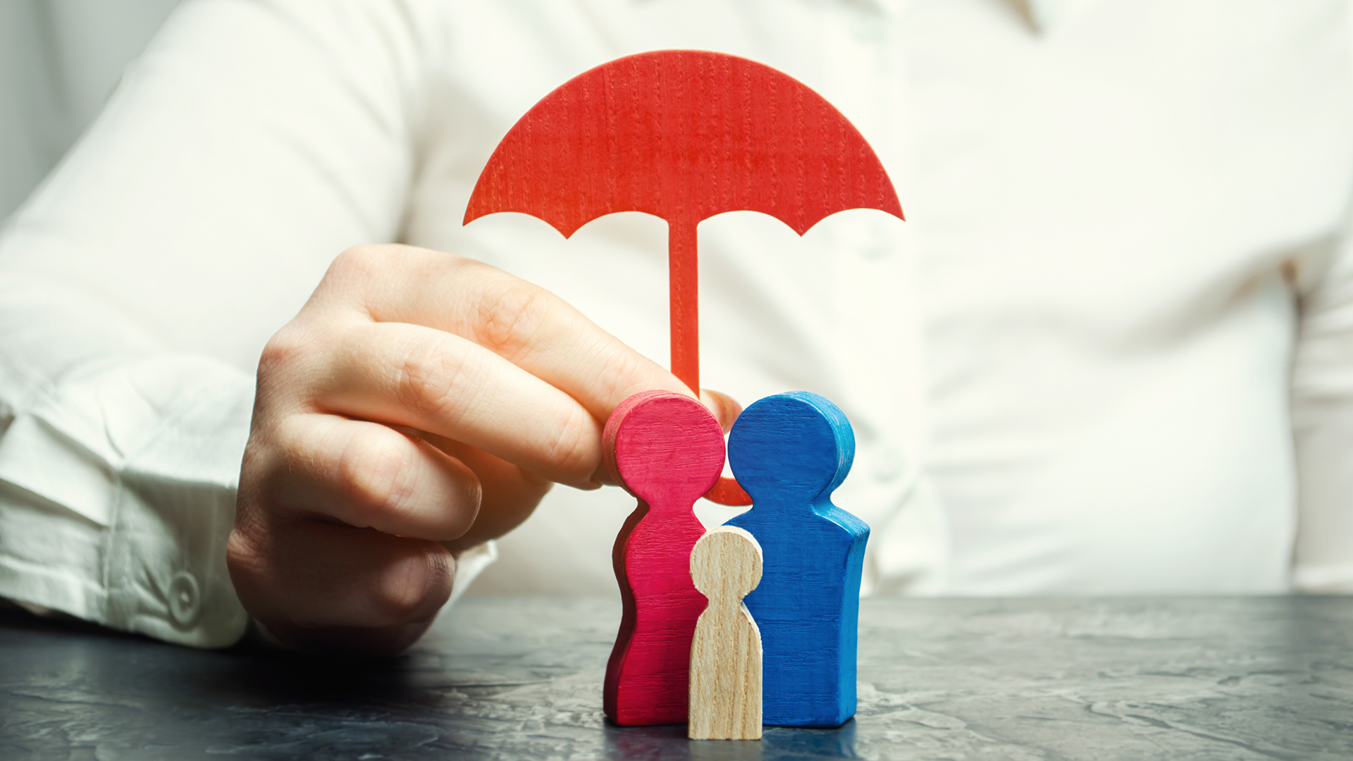 Wooden block family under umbrella