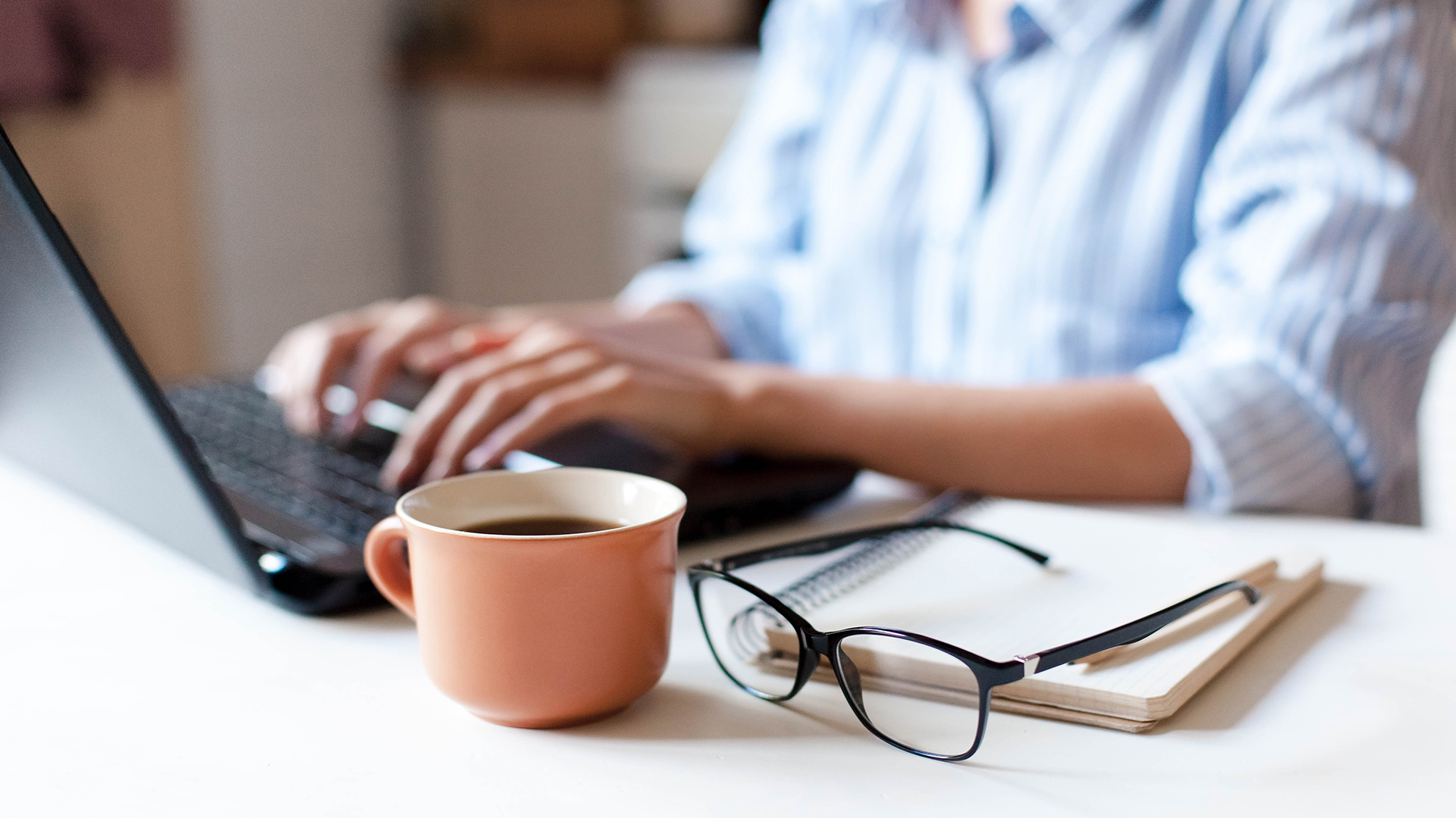 laptop, coffee cup and glasses on top of journal