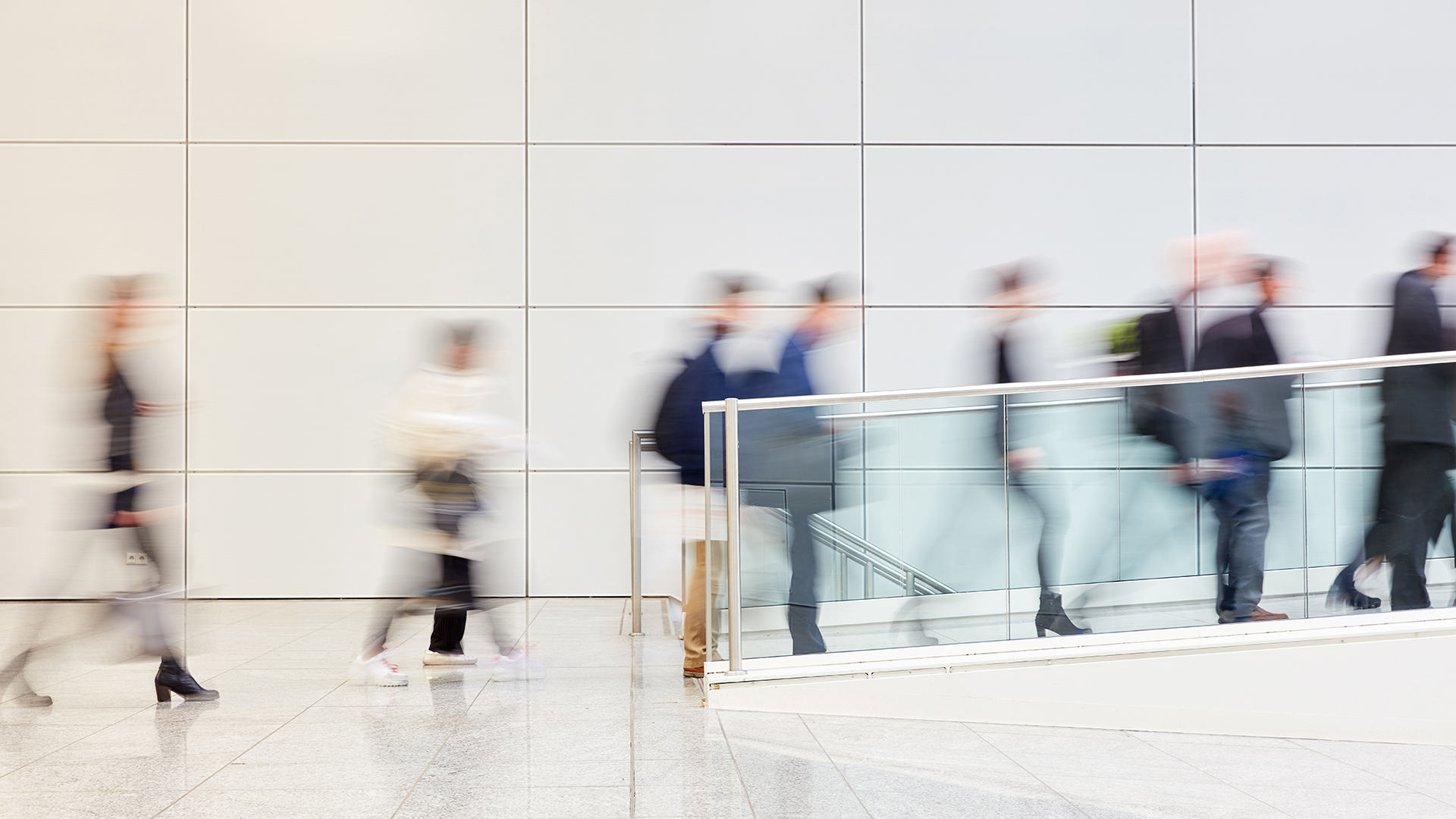 Many anonymous business people are walking through a bright corridor in the modern office