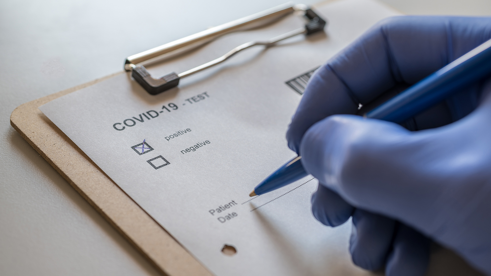 Gloved hand with COVID-19 checklist