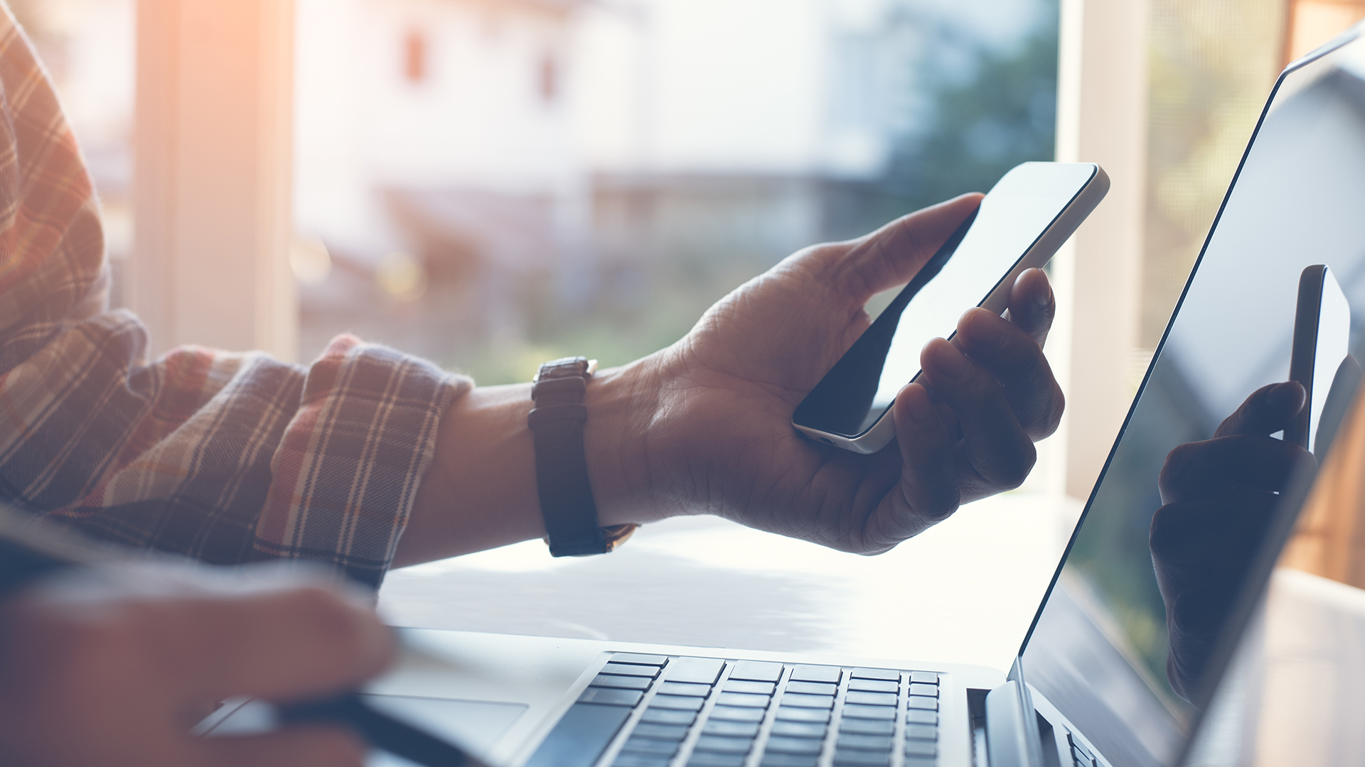 Close up of casual man or freelancer working on laptop computer and holding mobile smart phone with reflection on blank screen