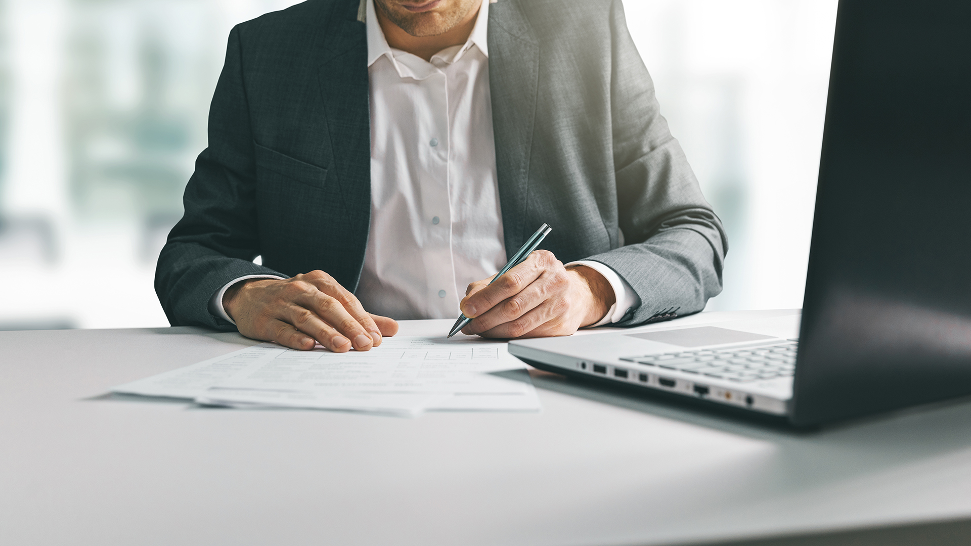 young man in suit writing business papers at desk