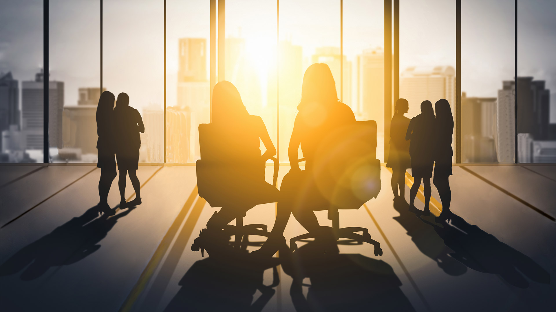 Women sitting and standing in a corporate setting
